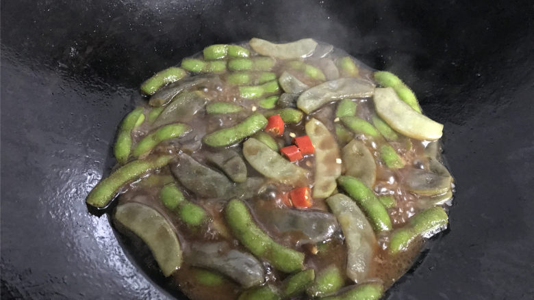 毛豆炒羊眼豆,放入一个红辣椒后加适量的水。