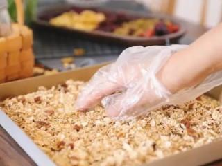 自制谷物麦片,然后把燕麦平铺在烤盘上