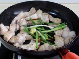 十味 红烧肉豆腐泡,锅里不放油,用中小火将肉炒至微微上色,然后将葱,姜、八角和红糖放入锅中炒。