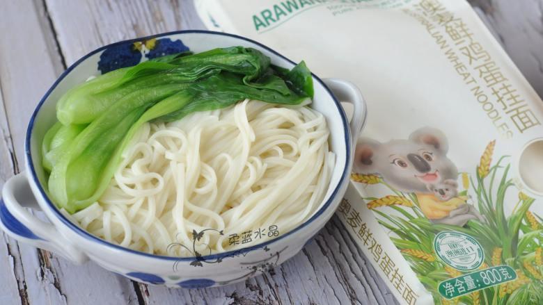 香辣肥肠面,将面捞出摆在碗中,上面放小油菜。