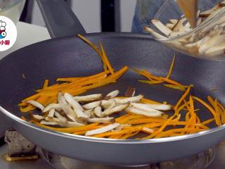 上海两面黄炒面,平底锅放入猪油1勺烧热,放入胡萝卜丝炒出红油,再放入香菇丝、青豆炒熟,加入咖喱牛肉酱,翻炒均匀制成浇头备用