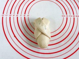 牛奶炼乳蔓越莓软欧,然后将左边的那条继续往面团右下方折,在底部将接口处捏紧。