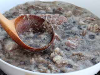 清炖牛肉萝卜汤,用勺子将表面的浮沫撇出来,然后捞出牛肉块