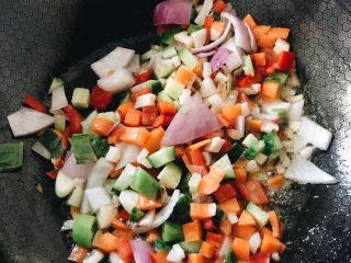 虾仁什锦炒饭,另起油锅,放入小洋葱丁炒香,再下胡萝卜丁翻炒,再放入其他蔬菜丁,加盐和味极鲜酱油,翻炒至入味