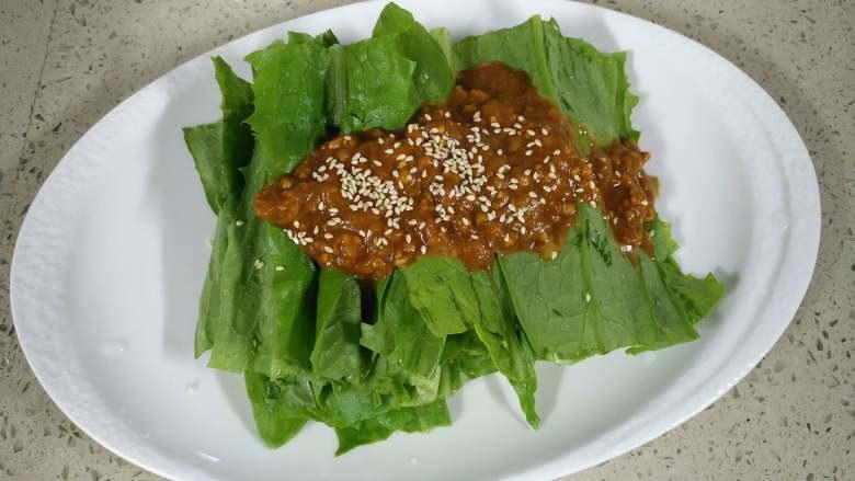 麻酱油麦菜,将调好的料汁倒入油麦菜上,撒上炒熟的白芝麻,拌匀就可以了。