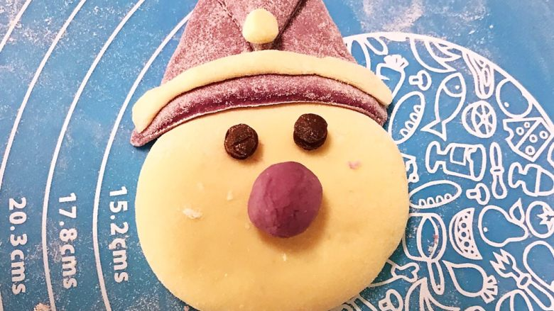 萌萌哒紫薯圣诞老人小馒头,开始组装,先把小白面球放在帽子上,把长条面压在帽子边缘,再加上两个眼睛,把鼻子放上去