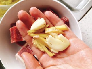 菌菇牛腩汤,将1颗蒜头、2片姜切成条状。