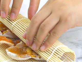 香甜柿子核桃卷,将柿子饼卷起,卷好后用皮筋固定,放入冰箱冷藏1小时定型