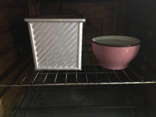 南瓜奶油吐司,放入烤箱进行二发,旁边放一碗开水辅助发酵。