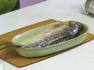 红烧鲤鱼,鲤鱼处理干净,加入料酒、盐,抹匀腌制片刻