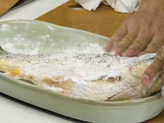 红烧鲤鱼,取出鲤鱼,稍微按揉表面,用厨房纸擦干水分,再裹上一层玉米淀粉,静置5分钟,而后烧热油锅,拍去鲤鱼表面多余淀粉,下入油锅煎炸至表面金黄,盛出备用