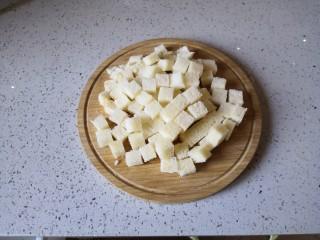 香橙烤吐司—清新香甜的早餐,将吐司的四边去除后切成小方块。
