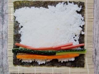 简易版寿司拼盘,把火腿肠、藕、黄瓜码上,放在下端三分之一处