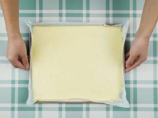 奇异果蛋糕卷,烤盘铺烘焙纸,倒入蛋糕糊铺平,轻震两下消除大气泡,然后放入预热好180℃的烤箱烤约15分钟