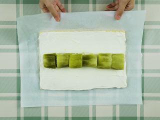 奇异果蛋糕卷,取出蛋糕片脱模,撕去烘焙纸,切平四边;将蛋糕片置于新的烘焙纸上,表面抹上奶油,摆上一排奇异果,卷起裹紧,放入冰箱冷藏2小时定型