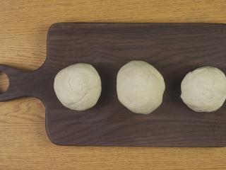 新疆烤馕,取出面团按揉排气,切分成三等份,全部揉圆,再盖上保鲜膜静置发酵10分钟