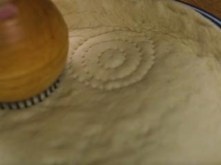 新疆烤馕,用馕戳在饼胚上压出花纹,表面刷层薄油,均匀撒上白芝麻,放入预热好230°C的烤箱烤制15-20分钟至颜色金黄
