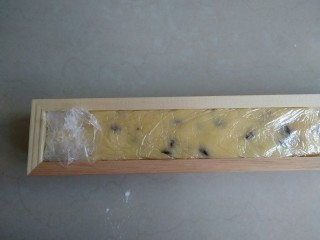 蔓越莓饼干,放在保鲜膜上,整理成长方形,放入冰箱冷冻一个小时。
