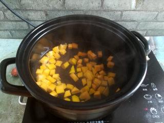 南瓜小米粥,砂锅烧开水后倒入南瓜,大火煮开