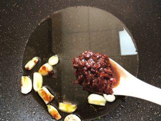鱼香杏鲍菇,锅中放油烧热,蒜瓣放进去加1汤匙红油豆瓣酱翻炒出红油