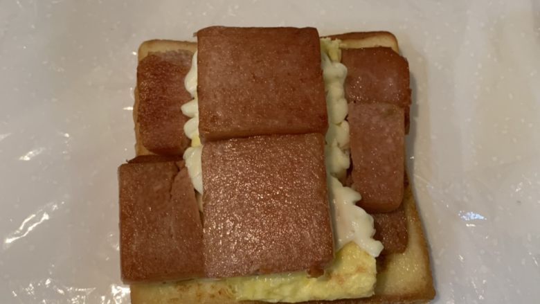 厚蛋烧芝士午餐肉三明治,铺上煎好的午餐肉