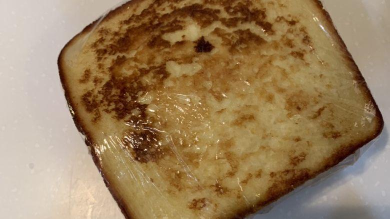 厚蛋烧芝士午餐肉三明治,盖上面包,把保鲜膜包紧,然后对半切开就可以吃了
