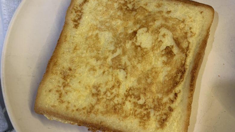 厚蛋烧芝士午餐肉三明治,煎好出锅,方块包下面铺一层保鲜膜
