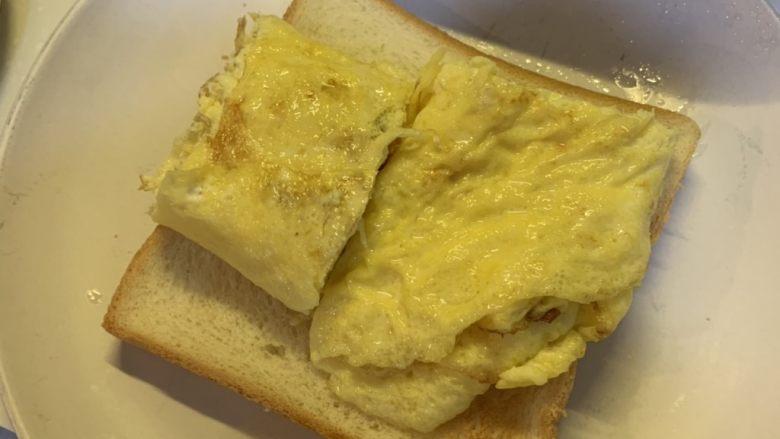 厚蛋烧芝士脆皮肠三明治,在烤好的吐司下面铺一层保鲜膜,放入煎好的蛋卷
