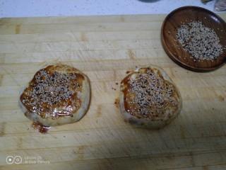 芝麻酱烧饼,卷起来平均分成2份,收紧口,用手按扁,表皮再均匀涂上芝麻酱,撒上芝麻,用手压一压。