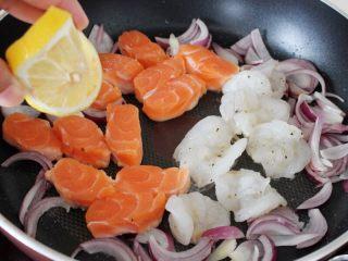 百变水果  三文魚虾仁芒果沙拉,然后将洋葱拔到边上,三文鱼和虾仁码入锅中,挤一点柠檬汁在鱼和虾的上面。
