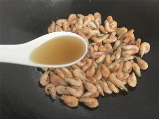 油爆河虾,快速翻炒至小河虾的颜色变红色后加入1勺料酒去腥。