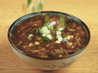 敲肉羹,待食材煮熟,盛出装碗,撒上葱花即可享用