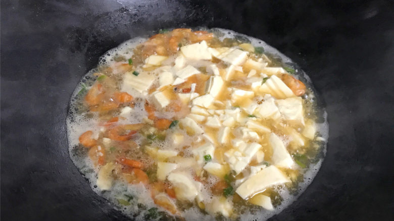 河虾豆腐汤,把盒中的豆腐用锅铲弄成小块后放入锅中一起煮开即可。