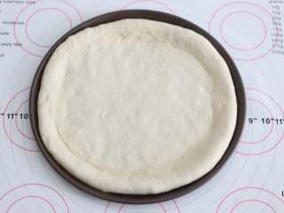 自制培根披萨,用擀面杖将面团擀成一个与披萨盘盘底一样大小的饼底,把饼皮铺进去。
