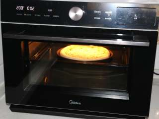 自制培根披萨,烤箱200度提前预热,预热好后将披萨饼底放入烤箱中层,烤3分钟。