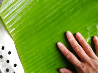 南瓜糯米糍,取一张油纸铺在蒸架上,我这里用的是芭蕉叶,所以抹了一层花生油防粘。