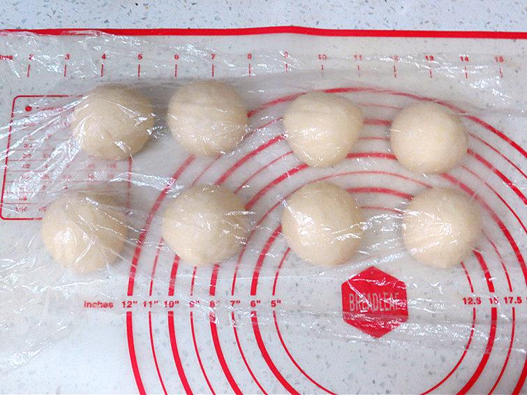 让人吃后难忘的葱多多面包【台式香葱包】,均匀的分成8份揉圆,盖上保鲜膜松弛醒发20分钟