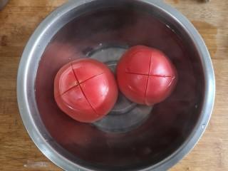 金针菇番茄龙利鱼,2个大番茄顶部划十字,顶部朝下放进碗中浇开水烫2-3分钟后剥去皮。