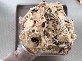 网红草莓雪花酥,将雪花酥料拿起来,用手反复柔和,拉丝,这样让棉花糖均匀的裹在坚果和饼干上,雪花酥就会更有嚼劲,而且也不会硬