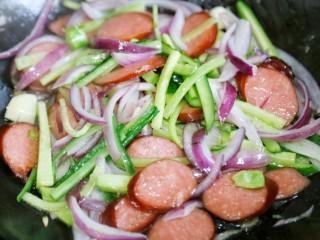 好吃到爆的火腿意面,再加入洋葱、黄瓜迅速翻炒。