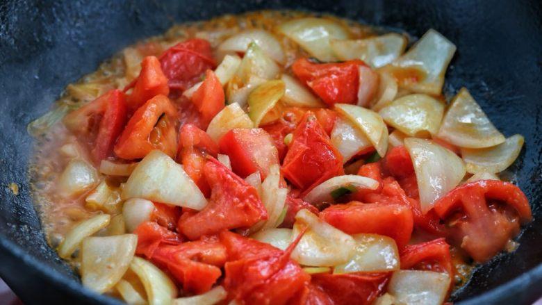 西红柿土豆炖牛肉,接着放入一半的番茄和洋葱,小火将番茄炒出汤汁。