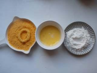 香酥鱿鱼圈,鱿鱼圈先在淀粉中滚一圈,再放到蛋液中滚一圈,最后沾满面包糠。