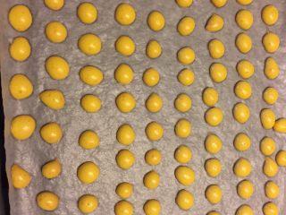 蛋黄溶豆,到时间,烤好的溶豆会非常容易从油纸上剥落,如果底部还是黏的,可以再烤2到3分钟。