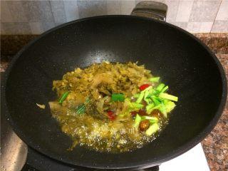 酸菜烧鲫鱼,放入酸菜、蒜苗头、泡姜和泡椒翻炒2分钟。