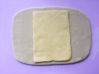 可颂热狗,冰箱取出冷冻的黄油片,用剪刀裁开保鲜袋,将黄油片放在面片中间