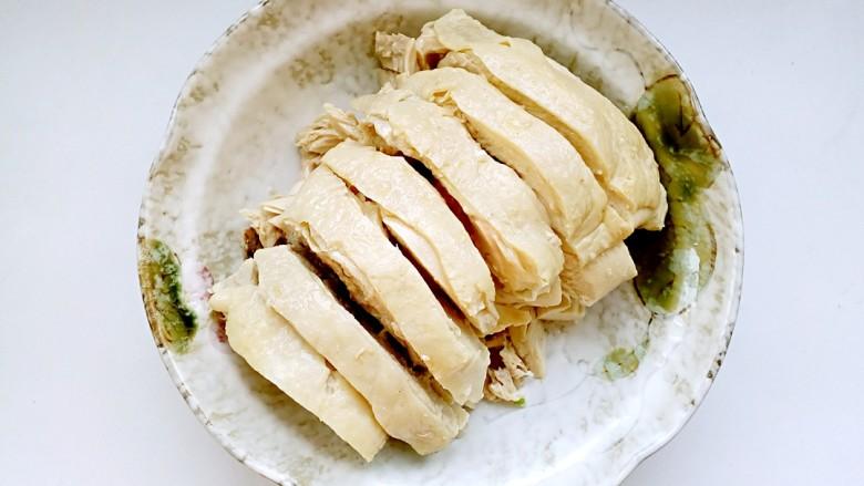 口水鸡,将冰镇好鸡腿切成块,码放在盘中。