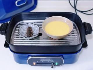 营养早餐 海参蒸蛋羹,美食锅中加入水,放入蒸屉,将蛋液碗与海参碟子放在蒸屉上。(一定将蛋液碗盖上盖子,或者包上耐高温的保鲜膜也可以)
