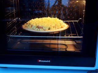 杂蔬火腿肠披萨,放入预热好的烤箱,上下火200度,中层烤15-20分钟,烤至表面芝士融化变成焦黄色即可