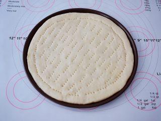 杂蔬火腿肠披萨,把面团取出按压排气,擀成跟披萨盘一样大小的圆形,放入披萨盘,用叉子在饼皮上叉些小洞