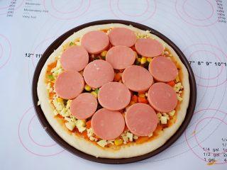 杂蔬火腿肠披萨,再放入胡萝卜、玉米粒、青椒、火腿片